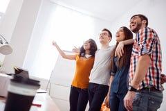 De vrolijke jonge collega's drukken positieve emoties uit Stock Afbeeldingen