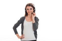 De vrolijke jonge donkerbruine vrouw van de vraagbeambte met hoofdtelefoons en microfoon die die op camera glimlachen op wit word Royalty-vrije Stock Afbeelding