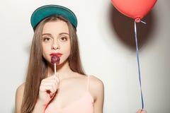 De vrolijke jonge gestileerde vrouw geniet van snoepje Stock Fotografie