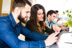 De vrolijke jonge groep freelancers werkt met vreugde in modern bureau Het bekijken telefoon en glimlach royalty-vrije stock fotografie
