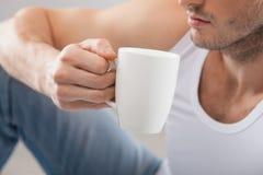 De vrolijke jonge kerel drinkt hete thee stock afbeelding