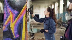 De vrolijke jonge kunstenaar van de vrouwen amateurgraffiti leert om met nevelverf van deskundige gebaarde schilder te werken ter stock footage