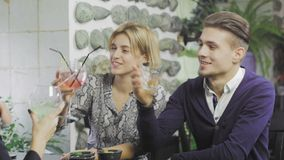 De vrolijke jonge man en de vrouwen dichte vrienden spreken terwijl het hebben van lunch in koffie stock footage