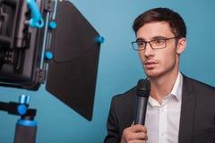 De vrolijke jonge mannelijke journalist rapporteert met Stock Afbeeldingen