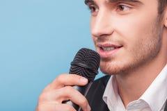 De vrolijke jonge mannelijke verslaggever vertelt nieuws Stock Afbeeldingen