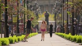 De vrolijke jonge mens koestert zijn schitterend meisje en leidt haar op gaan met een skateboard rijdend in slo-mo stock videobeelden