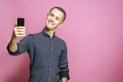 De vrolijke jonge mens maakt selfie op de camera van zijn telefoon en het glimlachen stock foto's