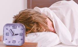 De vrolijke jonge mens is ontwaken na het slapen in de ochtend Mens het uitrekken zich in bed Ontspan in het bed stock afbeeldingen
