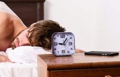 De vrolijke jonge mens is ontwaken na het slapen in de ochtend Voeten mensenslaap in comfortabel bed Vlakke ontwaken royalty-vrije stock afbeeldingen