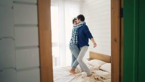 De vrolijke jonge minnaars dansen op pret in slaapkamer hebben en bed die thuis zorgeloos lachen De gelukkige moderne jeugd, stock video