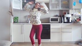 De vrolijke jonge mooie vrouw danst in keuken die pyjama's en hoofdtelefoons in de ochtend dragen luisterend aan muziek stock video