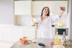 De vrolijke jonge vrouw bevindt zich in keuken en houdt kom met salade Zij registreert video en glimlacht op camera Het meisje ki stock afbeeldingen
