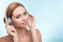 De vrolijke jonge vrouw gebruikt hoofdtelefoons met vreugde Stock Afbeelding