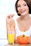 De vrolijke jonge vrouw heeft ontbijt Royalty-vrije Stock Foto's