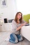 De vrolijke jonge vrouw ontspande thuis met laptop Stock Afbeeldingen