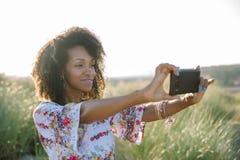 De vrolijke jonge vrouw van het afrokapsel bij het strand die foto nemen royalty-vrije stock foto