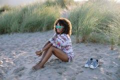 De vrolijke jonge vrouw van het afrokapsel bij het strand stock fotografie