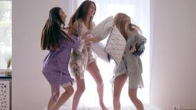 De vrolijke jonge vrouwen met kussens springen en hebben pret op bed tijdens een pyjamapartij in de slaapkamer stock footage