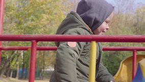 De vrolijke jongen beklimt stairse op speelplaats stock video