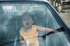 De vrolijke jongen binnen de auto geniet van reizend op vakantie Stock Foto