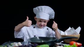 De vrolijke jongen danst en toont duimen terwijl het koken Hij draagt chef-kokskostuum en GLB stock footage