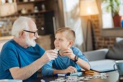 De vrolijke jongen die van Nice raadsels met zijn grootvader verzamelen Stock Afbeelding