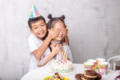 De vrolijke jongen gaat het mooie meisje met Verjaardag gelukwensen royalty-vrije stock fotografie