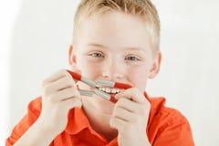 De vrolijke jongen houdt samen magneten door zijn gezicht Stock Afbeeldingen