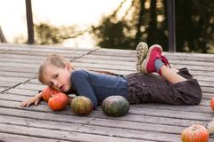 De vrolijke jongen ligt met pompoenen Stock Afbeelding