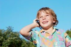 De vrolijke jongen met een mobiele telefoon stock fotografie