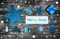 De vrolijke kaart van de Kerstmisgroet in blauw en wit met houten Si Stock Foto