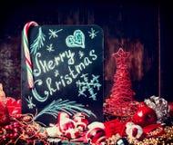 De vrolijke kaart van de Kerstmisgroet met snoepjes, het van letters voorzien en rode vakantiedecoratie Stock Foto's