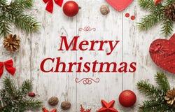 De vrolijke kaart van de Kerstmisgroet met tekst en Kerstmisdecoratie op witte houten raad Stock Foto