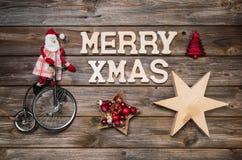 De vrolijke kaart van de Kerstmisgroet met tekst Rode Santa Claus op houten ru Stock Foto's