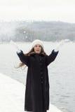 De vrolijke Kaukasische Jonge Vrouw in Sneeuwweer werpt snowbal Stock Afbeeldingen