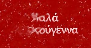 De vrolijke Kerstmistekst in het Grieks draait aan stof van linkerzijde op rode bac Stock Foto