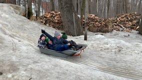 De vrolijke kinderen glijden onderaan de sneeuw op een slee Moskou, Rusland, Februari 2019 stock videobeelden