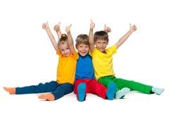 De vrolijke kinderen houden hun duimen tegen Stock Foto's