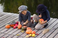 De vrolijke kinderen schilderen kleine Halloween-pompoenen Stock Fotografie