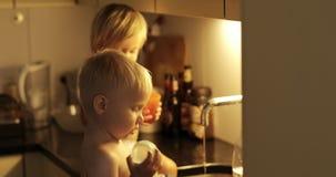 De vrolijke kinderen spelen in de gootsteen in de keuken stock footage