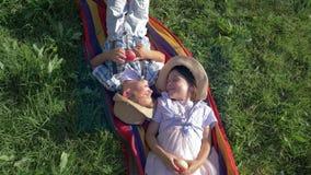 De vrolijke kinderen in strohoeden liggen op deken met appelen in hun handen en communiceren bij zomer stock footage