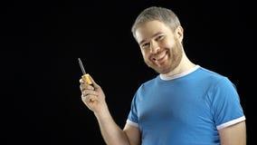 De vrolijke knappe mens in blauwe t-shirt houdt schroevedraaier DIY, reparatie, beginner, amateurbouw of het huisverbetering stock fotografie