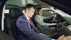 De vrolijke koper van de kerelauto spreekt aan professionele winkelbediendezitting binnen dure auto en wat betreft instrument stock videobeelden