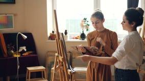 De vrolijke kunststudent werkt bij beeld het schilderen met borstel aan canvas terwijl haar leraar haar werk controleert en stock footage