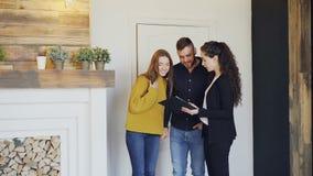 De vrolijke makelaar in onroerend goed ontmoet mooi jong paar in nieuw huis, opent deur, toont documenten en spreekt aan cliënten stock videobeelden