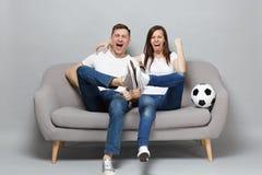 De vrolijke de man van de paarvrouw voetbalfans juichen steun omhoog favoriet team die met voetbalbal toe vuist dichtklemmen, die stock fotografie