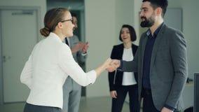 De vrolijke manager wenst geslaagde kandidaat na baangesprek geluk, schudden de mensen handen, die spreken en stock footage