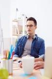 De vrolijke mannelijke arbeider verklaart plan van project Royalty-vrije Stock Afbeelding