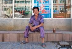 De vrolijke mens gekleed in pyjama zit buiten zijn huis, Tongliao, China Royalty-vrije Stock Foto's