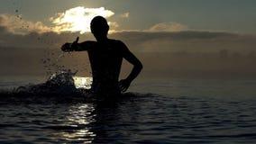 De vrolijke mens heft stromen van water in een meer bij zonsondergang in slo-mo op stock videobeelden